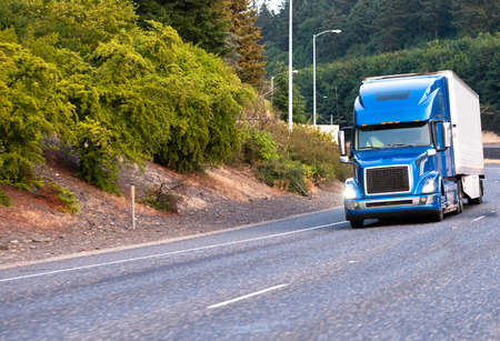 Blue modern popular huge comfortable big rig semi truck with turn on headlights haul reefer semi trailer for food delivery moving on wide turning highway with green trees on the shoulder