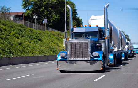 Icon of style. A classic American bonneted big rig semi truck with high tailpipes and chrome parts majestically pulls the trailer for concentrated loads and rides ahead of the convoy of other trucks with various types of semi trucks and trailers and goods Banque d'images