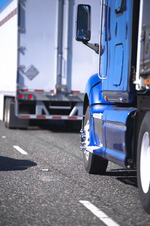 Modernas plataformas grandes semi camiones de diferentes marcas y modelos con remolques se mueven en un convoy uno por uno, llevando varios cargamentos a lo largo de la red de carreteras de América y Canadá, aseguran la actividad vital del país y la producción