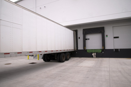 Long full-sized semi trailers stand it row at the dock gates of a large industrial warehouse loading and unloading the delivered goods and cargo that will be delivered after loading.
