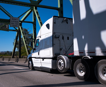 Hardy powerful big rig semi truck with a long dry van trailer moves through the arch bridge with metal triangular structures truss to the point of destination for timely delivery of cargo. The inscription on the bridge warns of a fine for texting while mo