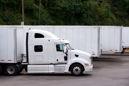 A stylish modern white big rig semi truck with a large comfortable cabin and a powerful engine with dry van trailer stands in line with other trailers on the parking lot in anticipation of the loading time of the trailer and delivery of the cargo to the d