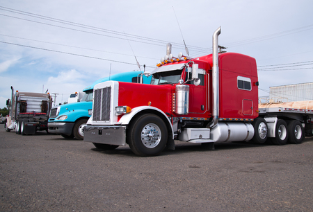 Powerful heavy-duty big rig red and blue classic and modern semi trucks with flat bed trailers  are parked in an industrial production park at the end of the working day