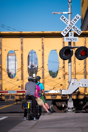 A group of bicyclists on bicycles stopped in a city street on a closed railway crossing while waiting for the freight train to pass