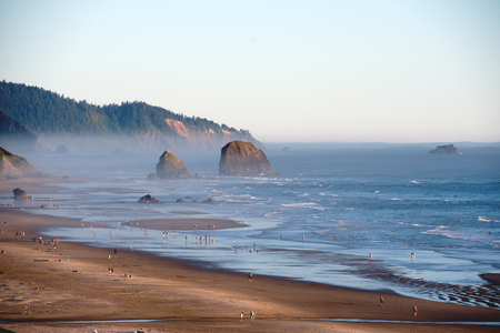 A breathtaking voluminous landscape of the Pacific coast in the Northwest, a bank with rocks steeped in the gray haze of sea dust with rocks sticking out of the water and a lot of people walking along the shore Stock Photo