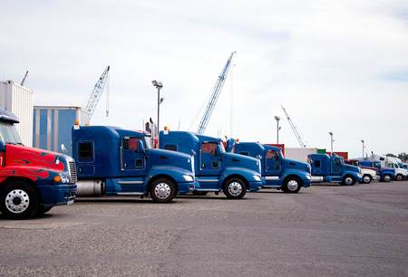 Bonnet semi trucks of different colors, models and designs for different uses for the purpose with different trailers are parked in row in anticipation of loading in an industrial production park