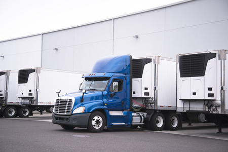 A big rig semi truck with a reefer trailer stands near the gate of the warehouse next to other reefer trailers that are loaded and unloaded to deliver perishable and frozen food to consumers