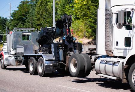 強力なビッグリグ半トラック トラクター tows 修理、修飾された機械工の専門修理店で診断サイトの緑の木々 と高速道路で壊れた白半トラック
