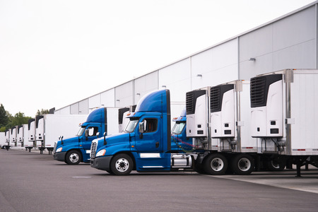 A day cab big rigs semi trucks with a reefer trailers stand near the gate of the warehouse next to other reefer trailers that are loaded and unloaded to deliver perishable and frozen food to consumers