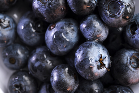 Appetizing healthy delicious and aromatic berries of blueberries shimmer with all shades of dark, reflecting the glare of light in droplets of dew