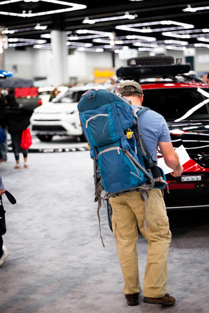A man in a baseball cap with a large tourist backpack is studying the map of the car show, as a real tourist in the forest checks his azimuth route for a successful journey