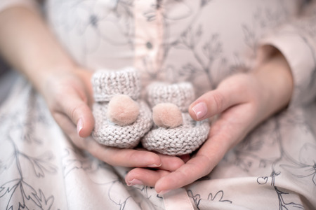 The future mother - a pregnant woman with a rounded belly prepares for the birth of the child and holds in her hands small knitted woolen shoes Stock Photo