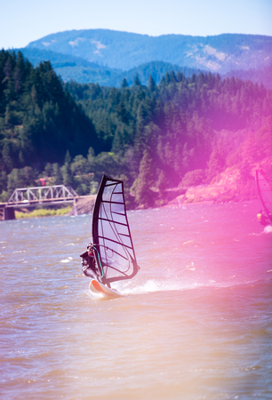 The surfer enjoying a walk with sail under the fresh summer wind along the Columbia River in the picturesque Columbia Gorge in the Hood River - the center of windsurfing as a professional sport, and the resting place for windsurfing lovers