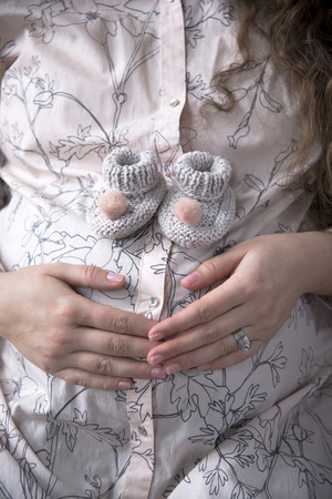 The future mother - a pregnant woman prepares for the birth of the child and holds her hands on rounded belly with small knitted woolen shoes standing on