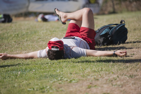 A young man in a T-shirt and shorts sunbathing in the sun lying on the grass and hands spreading does not part with the mobile phone lying on his chest, even during rest.