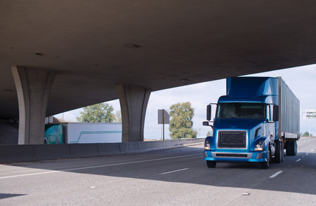 Modern big rig blue semi truck with tall cabin transporting dry van semi trailer going under overpass concrete bridge with powerful support poles across the highway road delivering commercial goods to different business customers