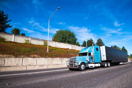 Blue modern big rig long distance semi truck with protective grille guard and black covered trailer for commercial cargo transportation running on straight wide highway in good weather day with blue sky