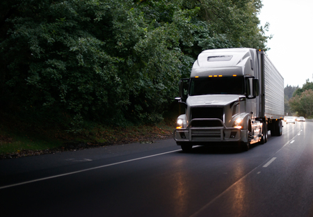 White modern big rig semi truck with grille guard and turn on headlights and reefer semi trailer running on evening road with green trees and light reflection on the road surface Standard-Bild