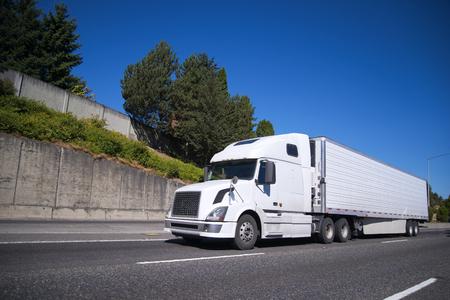 Camion moderno bianco semi grande rig con semirimorchio reefer dotato di unità di refrigerazione andando su ampia autostrada piatta con carico commerciale per la consegna al magazzino