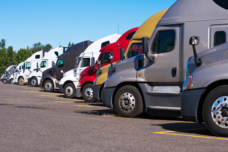 Big rigs semi trucks of different colors makes and models stand in row on truck stop parking lot for truck driver rest according to log book  Editorial