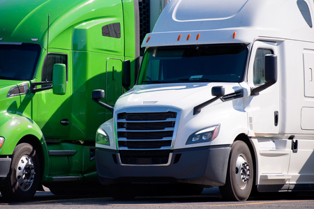 Green and White Big rigs semi trucks of different makes and models stand in row on truck stop parking lot for truck driver rest according to logbook delivery schedule Stock Photo