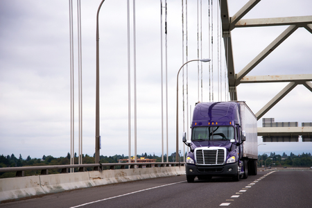 Modern purple reliable American big rig semi truck with dry van semi trailer for long haul cargo delivery running on highway along big arch Fremont bridge  Stok Fotoğraf