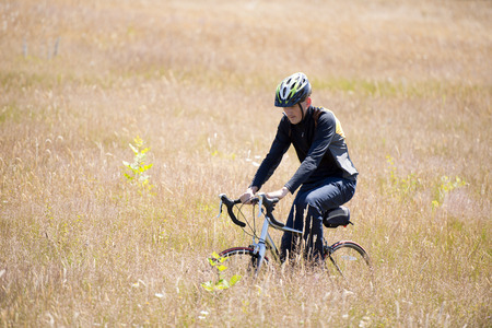 A cyclist in a helmet rides on the bike along a field with tall grass and wildflowers moving forward and leaving a trail on the grass, leaving the city bustle to meet nature, preferring an active rest and a healthy lifestyle