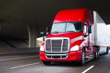 Um caminhão semi-moderno de grande porte para transporte de longa distância com uma cabine alta para melhorar as características aerodinâmicas move-se sob a ponte através de uma rodovia de várias faixas transportando um semi-reboque van seco com carga comercial até o local de entrega