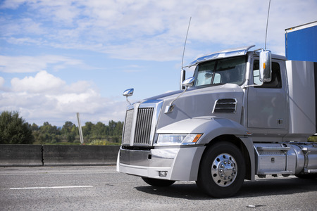 Modern grey big rig day cab semi truck for local deliveries and haul with covered semi trailer going on the wide road with safety fence and trees on background