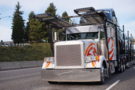 Classic big rig semi truck with square grille and two story compact car hauler semi trailer running on the road to unloading transporting to point of destination vehicles 스톡 콘텐츠