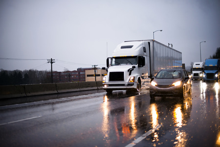 Heavy traffic with big rig semi trucks convoy with semi trailers transporting commercial cargo and another cars on highway in rain evening with headlight reflection on wet surface