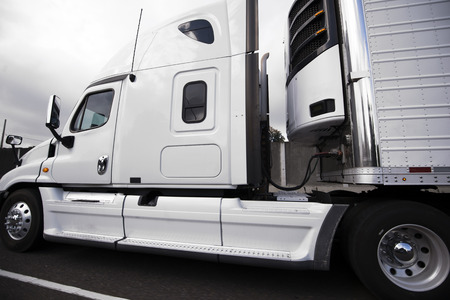 White bonnet American big rig semi truck with reefer semi trailer and refrigerator unit on it running on the road transporting perishable products