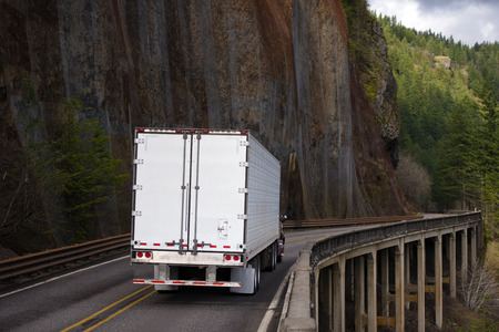 Big rig semi truck with long refrigerator semi trailer carry commercial cargo and moving on bridge with support poles on side of big rock wall in Columbia Gorge area