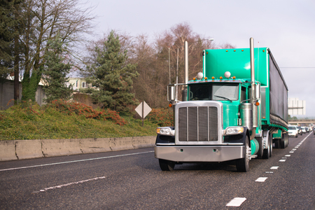 Green classic big rig semi truck with chrome accessories and stainless steel pipes transporting long covered semi trailer with aerodynamic spoiler moving on the wide multiline road in front of another traffic