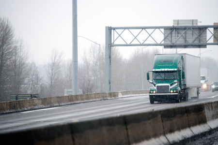 Big rig green American semi truck with dry van semi trailer driving on winter slipper road with snowy storm weather delivering commercial cargo to point of destination