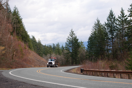 Big rig semi truck with turning conveyor belt mechanism for comfort and quick loading and unloading commercial cargo driving by winding road with forest hills