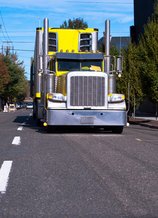 Bright yellow American classic big rig semi truck fleet with freezer semi trailer and tall chrome exhaust pipes running by urban city street for timely delivery of goods to the customers Imagens