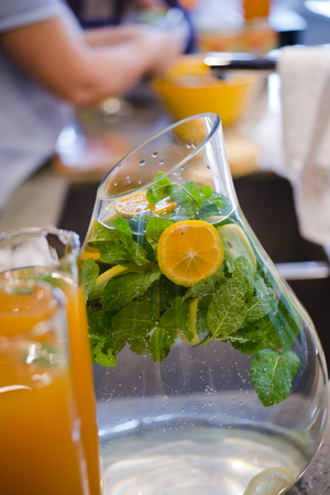 Delicious healthy exotic nature refreshing drink with mint leaves and sliced lemon in a glass decanter have a wonderful taste and a light aroma of mint and citrus create an excellent atmosphere of celebration and relaxation at the same time Stock Photo