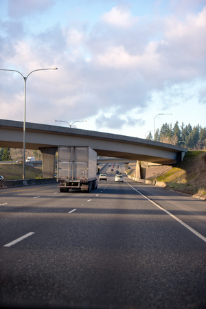 Big rig semi truck with dry van semi trailer going under the bridge across multiline divided highway at sunny day with cloudy blue sky