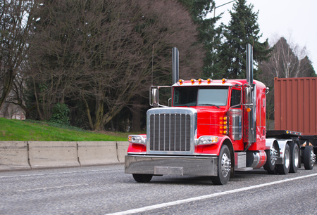 Bright red power classic American big rig semi truck with tall chrome exhaust pipes transporting container on flat bed semi trailer on wide multiline highway with trees on background