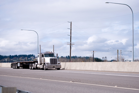 Big rig classic American idol semi truck tractor with day cab for local commercial cargo deliveries transporting empty flat bed semi trailer on wide highway driving to warehouse for loading Stock Photo
