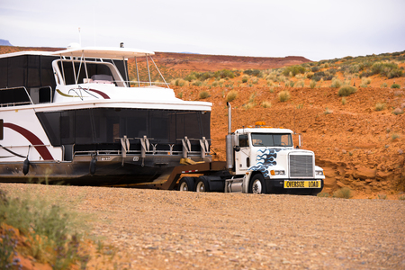Big powerful American bonnet rig semi truck with sign oversize load transporting down the red rocks hill to the water a huge oversize multilevel ship on marine resort at Lake Powell in Page Arizona Stock fotó