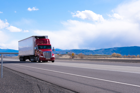 Big rig American bonnet powerful red semi truck with refrigerated semi trailer with refrigerator unit for cooling trailer inside space transporting commercial cargo on flat road in Utah Stock Photo - 100479537