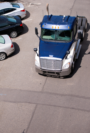Big rig dark blue American bonnet powerful semi truck tractor without semi trailer running on the parking place with small car parking on the side