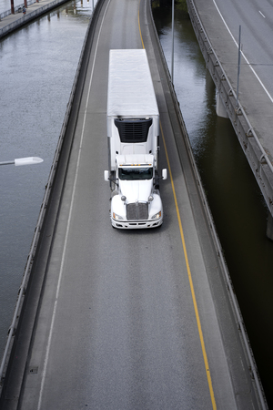 Big rig American semi truck transporting commercial cargo in refrigerated semi trailer with refrigerator unit by separated overpass road intersection along the river with support pillars in the water