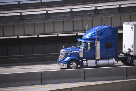 Big rig blue American semi truck transporting commercial cargo in covered dry van semi trailer going under multilevel overpass roads intersection with support pillars along the each other