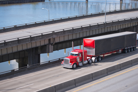 Big rig red classic American semi truck transporting commercial cargo in covered dry van semi trailer going under multilevel overpass roads intersection along the river with support pillars in the water