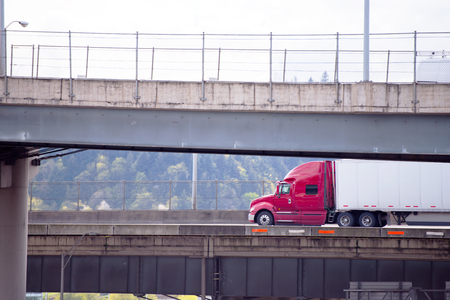 Big rig red classic American semi truck transporting commercial cargo in covered dry van semi trailer going under multilevel overpass road intersection with support pillars along the hill with forest