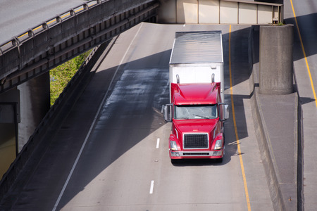 Big rig red American semi truck transporting commercial cargo in covered dry van semi trailer going under turning overpass road intersection along the river with support pillars in the water