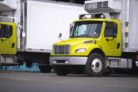 Small semi truck with box trailer and refrigeration unit for local delivery of cooled food stand for relevant safety carry standing at warehouse dock for loading cargo
